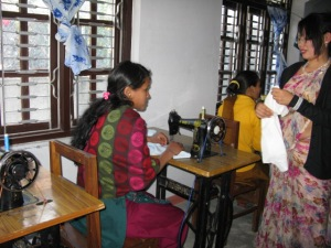 Mentoring through imparting a skill. Nepali women learn sewing from Lily.
